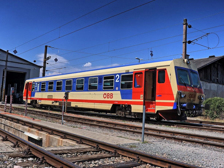 Alte Diesel-Fahrzeuge vom Typ ÖBB 5047 mit mehreren Stufen beim Einstieg.